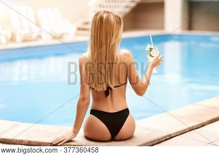 Sensual Woman In Bikini Having Refreshing Drink At Poolside On Summer Day, Back View