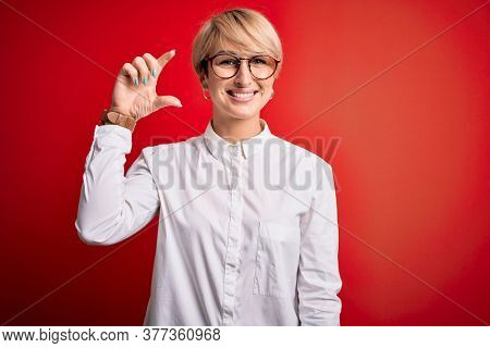 Young blonde business woman with short hair wearing glasses over red background smiling and confident gesturing with hand doing small size sign with fingers looking and the camera. Measure concept.