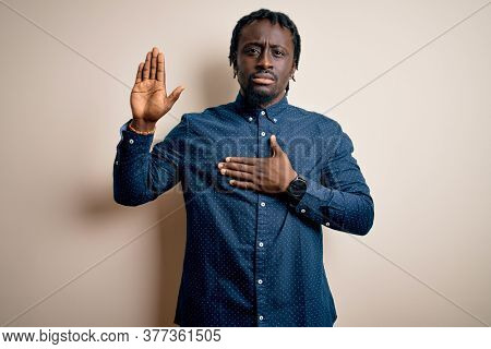 Young handsome african american man wearing casual shirt standing over white background Swearing with hand on chest and open palm, making a loyalty promise oath