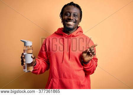 Young african american sporty man wearing sweatshirt with hoodie drinking bottle of water very happy pointing with hand and finger to the side