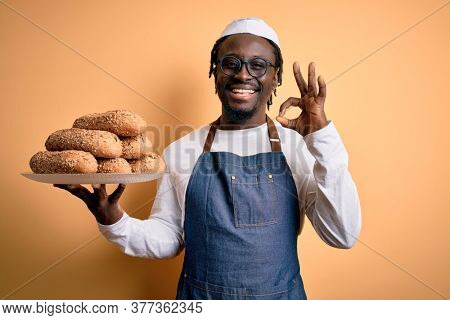 Young african american bakery man holding tray with healthy wholemeal bread doing ok sign with fingers, excellent symbol