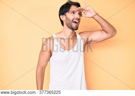 Handsome hispanic man wearing summer look and sunglasses very happy and smiling looking far away with hand over head. searching concept.