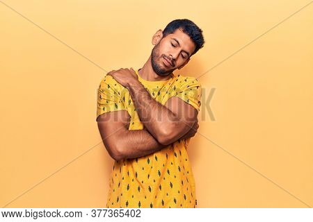 Young latin man wearing casual clothes hugging oneself happy and positive, smiling confident. self love and self care