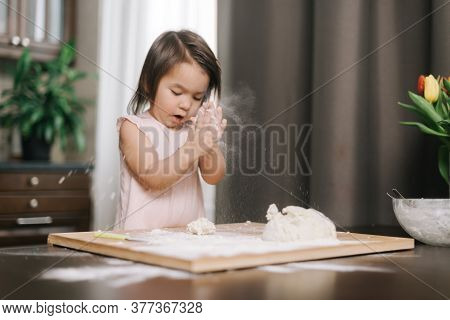 Beautiful Little Girl Is Clapping Hands With Flour. Child Is Playing With Flour In The Kitchen While