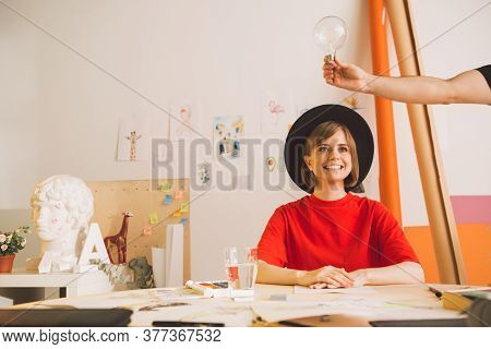 Young Pretty Smiling Girl Artist In Hat Thinks And Idea Comes In Studio. Insight Is Symbolized By A