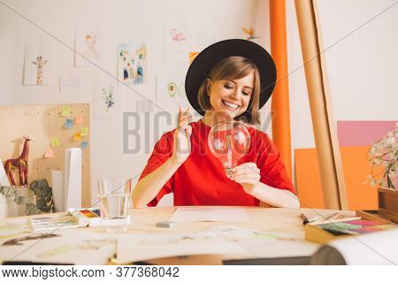 Young Happy Pretty Girl Artist In Hat With Light Bulb In Hands. Concept Photography About Inspiratio