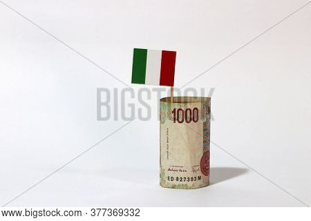 Rolled Banknote Money One Thousand Lire Italy And Stick With Mini Italia Nation Flag On White Backgr