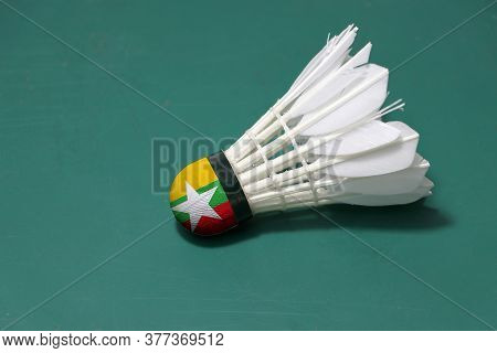 Used Shuttlecock And On Head Painted With Myanmar Flag Put Horizontal On Green Floor Of Badminton Co