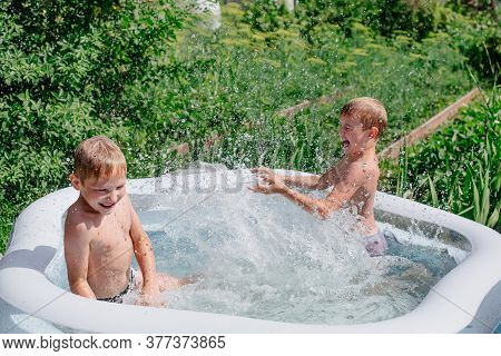 Two Boys Are Playing In A Home Inflatable Pool. Backyard Games.