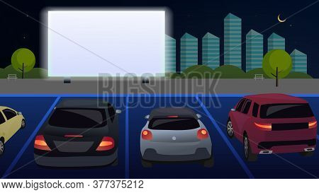People In Cars Watch A Movie In An Open Parking Lot At Night. Open Air Cinema For Street Cars. A Mov