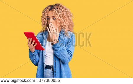 Young blonde woman with curly hair using touchpad device covering mouth with hand, shocked and afraid for mistake. surprised expression