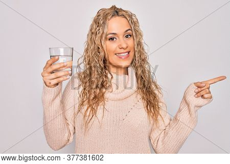 Young beautiful blonde woman drinking glass of water over isolated white background Smiling happy pointing with hand and finger to the side