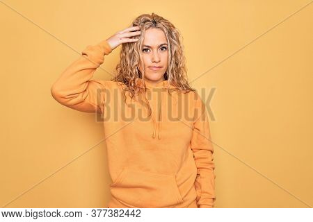Young beautiful blonde sporty woman wearing casual sweatshirt over yellow background worried and stressed about a problem with hand on forehead, nervous and anxious for crisis
