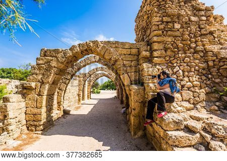 Enthusiastic woman takes pictures of the picturesque ruins of the ancient seaport of Caesarea. Excursion to the Archaeological Park in Israel. Concept of historical and phototourism