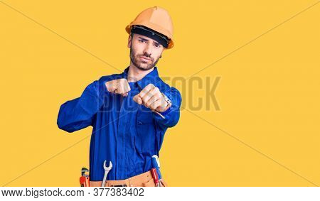 Young hispanic man wearing worker uniform punching fist to fight, aggressive and angry attack, threat and violence