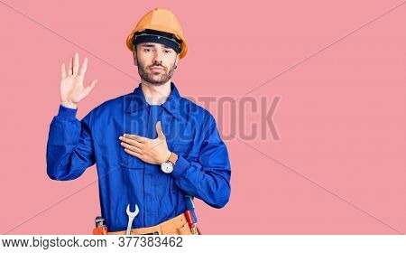 Young hispanic man wearing worker uniform swearing with hand on chest and open palm, making a loyalty promise oath