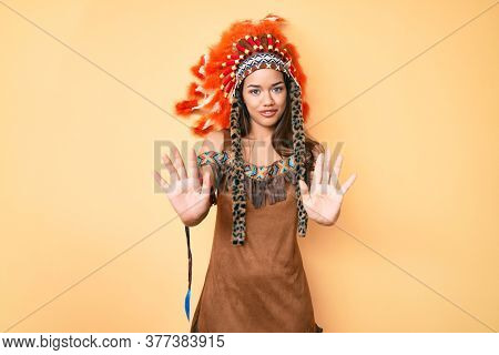 Young beautiful latin girl wearing indian costume moving away hands palms showing refusal and denial with afraid and disgusting expression. stop and forbidden.