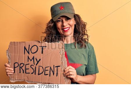 Middle age brunette communist woman holding banner with not my president message looking positive and happy standing and smiling with a confident smile showing teeth