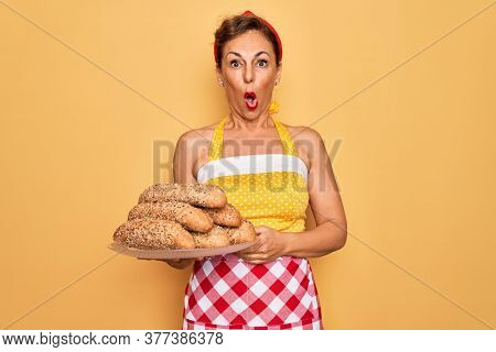 Middle age senior housewife pin up woman wearing 50s style retro dress cooking wholemeal bread scared in shock with a surprise face, afraid and excited with fear expression