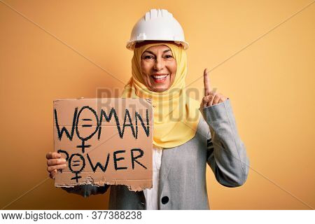Middle age architect woman wearing muslim hijab holding banner with women message surprised with an idea or question pointing finger with happy face, number one