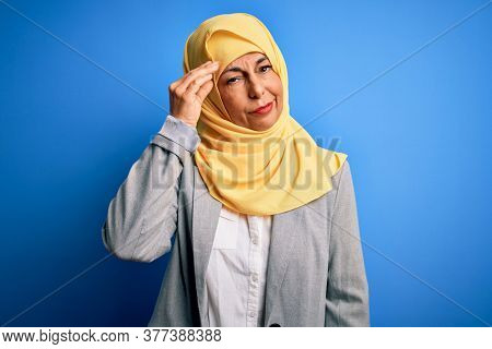 Middle age brunette business woman wearing muslim traditional hijab over blue background worried and stressed about a problem with hand on forehead, nervous and anxious for crisis