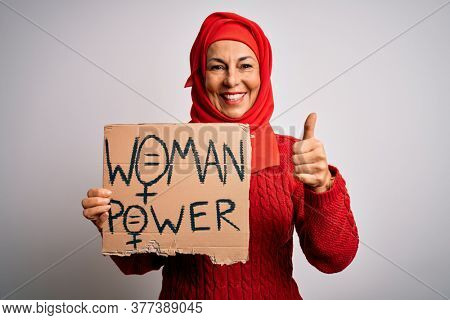 Middle age woman wearing muslim hijab asking for women rights holding banner happy with big smile doing ok sign, thumb up with fingers, excellent sign