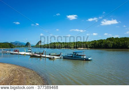 Krabi, Thailand - February 12, 2020: Pier on Krabi river with several long tail boats. Mangrove forest and karst scenery under blue sky