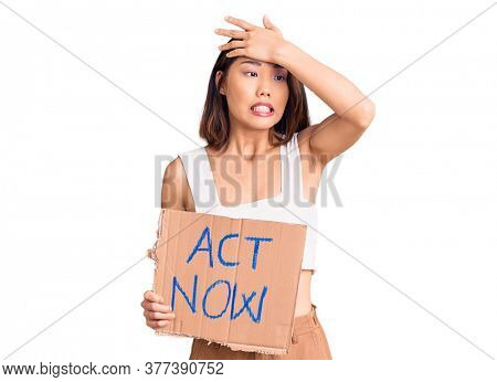 Young beautiful chinese girl holding act now banner stressed and frustrated with hand on head, surprised and angry face