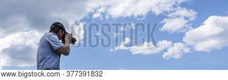 A Male Photographer Shoots And Photographs The Sky. Beautiful Panorama With Clouds