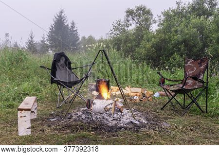 Bonfire In Nature. The Kettle Is Warming In The Flame. Cozy Outdoor Camping In A Clearing In The For