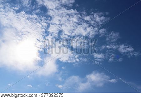 Cirrus Clouds In A Blue Sky, Taken On A Summer Day. The Sun Shines Through A Cloud