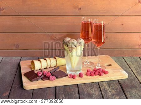 Glasses Of Rose Champagne, Waffle Cones With Chocolate Ice Cream In Glass As Stand, Pieces Of Dark C