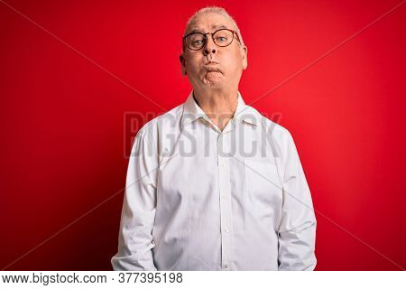 Middle age handsome hoary man wearing casual shirt and glasses over red background puffing cheeks with funny face. Mouth inflated with air, crazy expression.