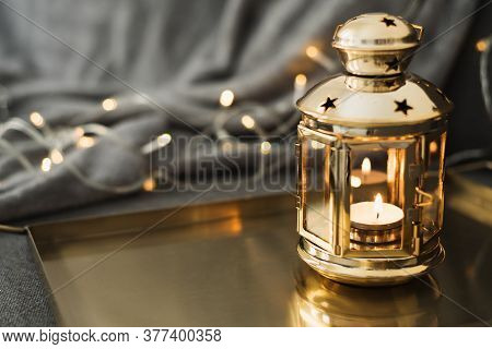 Golden Lantern With Burning Candle Standing On A Metal Tray, Decorative Lights As Background. Festiv