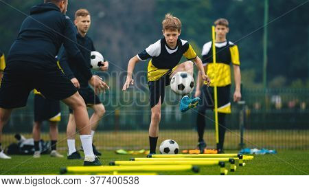 Teenage Boys On Football Training Session With Two Young Coaches. Junior Level Soccer Player Kicking
