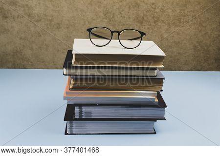 Black-rimmed Glasses Lie On A Pile Of Books. Blue Background