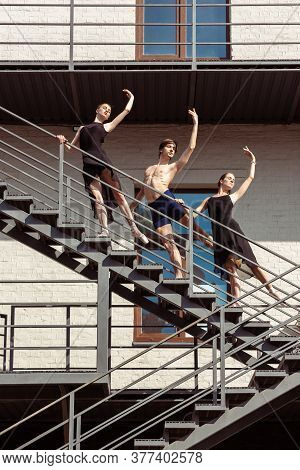 The Group Of Modern Ballet Dancers Performing On The Stairs At The City. Fast Moving Of Citylife, Gr