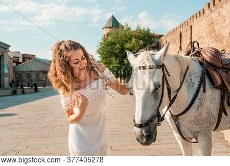Close Up Girl Female With A Horse In The Background Of City Streets. Happy Woman In White Dress With
