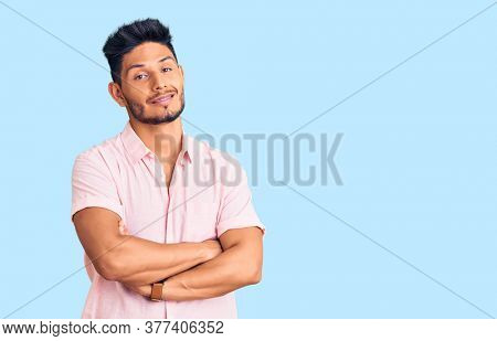Handsome latin american young man wearing casual summer shirt happy face smiling with crossed arms looking at the camera. positive person.