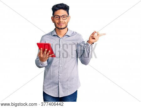 Handsome latin american young man holding touchpad smiling happy pointing with hand and finger to the side