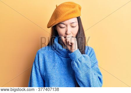 Young beautiful chinese woman wearing turtleneck sweater and french beret feeling unwell and coughing as symptom for cold or bronchitis. health care concept.