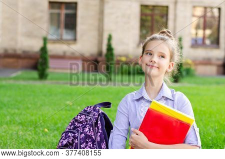 Back To School. Education Concept. Cute Smiling Schoolgirl Sitting On Grass. Happy Little Girl Child