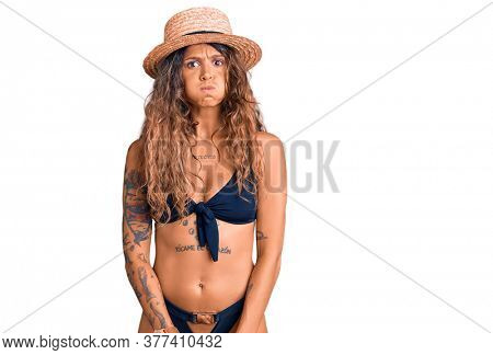 Young hispanic woman with tattoo wearing bikini and summer hat puffing cheeks with funny face. mouth inflated with air, crazy expression.