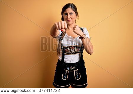 Young beautiful brunette german woman celebrating Octoberfest wearing traditional dress Punching fist to fight, aggressive and angry attack, threat and violence