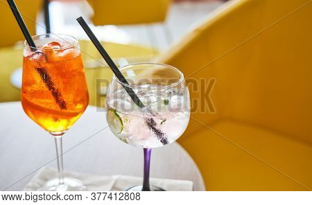 Glass of cold refreshing aperol spritz and gin tonic cocktail on table in summer.