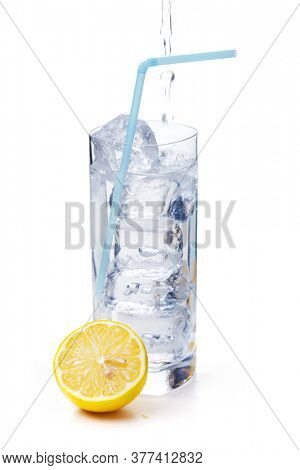 Water being poured into a glass with ice cubes and straw, orange next to it. Isolated on white.