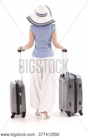Young woman in summer outfit and hat standing with two suitcases, rear view. Isolated on white.