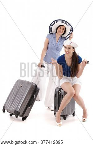 Two casual young woman in summer outfit, sitting on suitcase, pulling suitcase, looking at camera, smiling. Isolated on white.