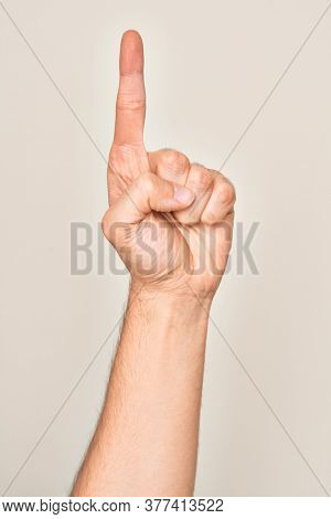Hand of caucasian young man showing fingers over isolated white background counting number one using index finger, showing idea and understanding