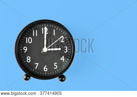 The Clock Is Black At 15 O\'clock Or 3 O\'clock. Top View In Blue Background. Clipping Path.